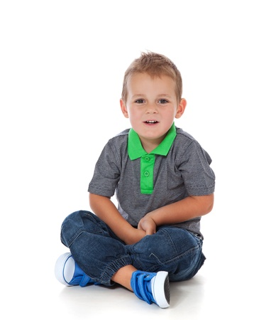 Volledige lengte shot van een schattige kleine jongen zittend op de vloer