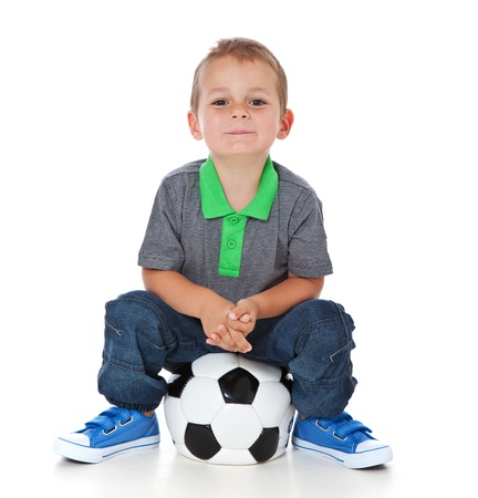 Full length shot of a cute little boy sitting at a soccer ball  All isolated on white background  photo
