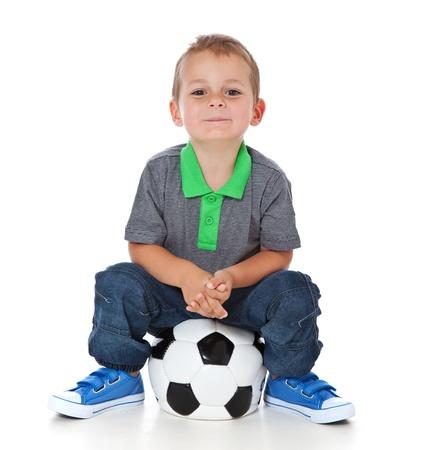 Volledige lengte shot van een schattige kleine jongen zit aan een voetbal Alle geïsoleerd op witte achtergrond Stockfoto