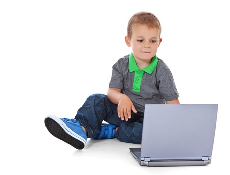 enquiring: Full length shot of a cute little boy sitting on the floor with computer  All isolated on white background