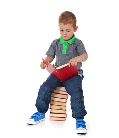 enquiring: Full length shot of a cute little boy sitting on a pile of books, reading  All isolated on white background