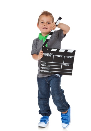 enquiring: Full length shot of a cute little boy holding a clapperboard  All isolated on white background