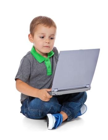 assis par terre: Tir sur toute la longueur d'un petit gar�on mignon assis sur le sol avec un ordinateur Tous isol� sur fond blanc