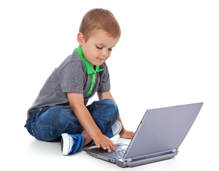 Full length shot of a cute little boy sitting on the floor with a computer  All isolated on white background  photo