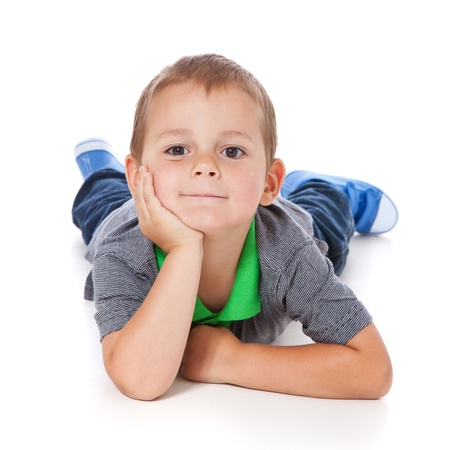 Full length shot of a cute little boy lying on the floor  All isolated on white background  photo