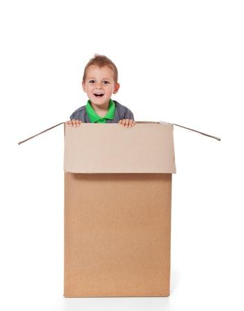 Schattige kleine jongen zitten in een doos Alle geïsoleerd op witte achtergrond
