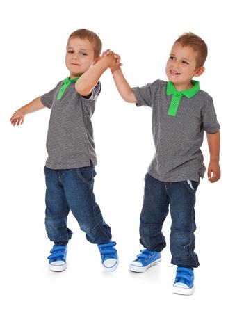 Volledige lengte shot van tweelingbroers plezier Alle geïsoleerd op witte achtergrond