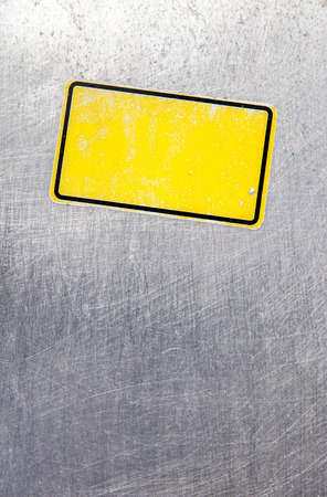stainless steel background: Yellow badge on stainless steel background