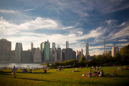 citylife: New Yorker enjoying the sunset at Brooklyn Bridge Park Editorial