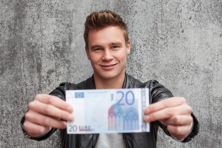 20 euro: Casual young guy holding 20 euro note Stock Photo