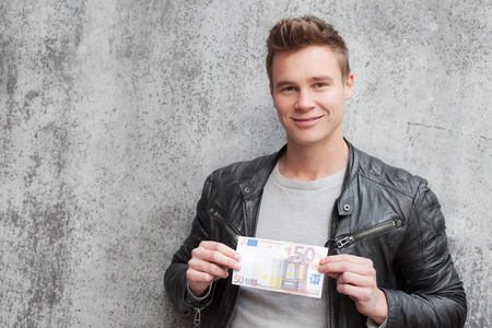 young guy: Casual young guy holding 50 euro note