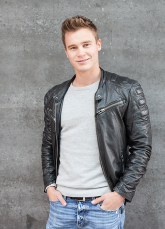young guy: Casual young guy in front of concrete wall