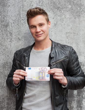 50 euro: Casual young guy holding 50 euro note
