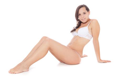 women sitting: Attractive girl in underwear. All on white background Stock Photo