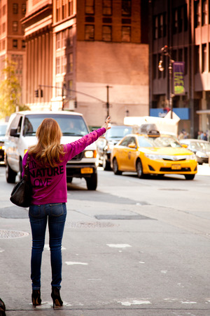 yellow cab: Young woman waving for yellow cab