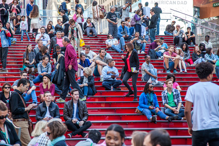 times square new york: People resting on famous red stairs on Times Square New York City Editorial