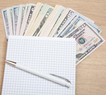 Various dollar notes next to notepade