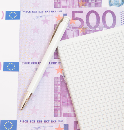euro notes: Notepad next to various euro notes Stock Photo