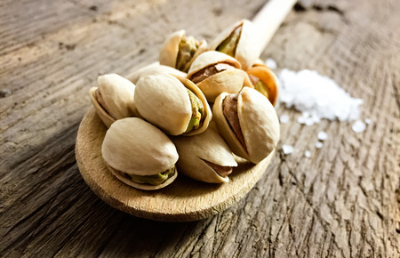 pistachios: Roasted and salted pistachios on wooden board