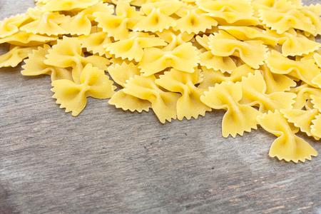 Fine farfalle noodles on wooden board 免版税图像