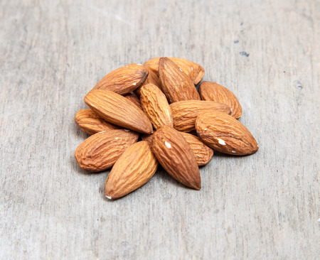 Fine almonds on wooden background