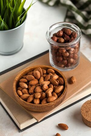 nuts in a wooden plate and a glass jar on a light background with green accents in the background Stock Photo