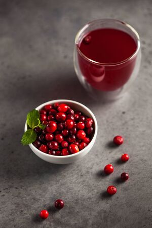 cranberry juice and ripe cranberries in a bowl on a gray background
