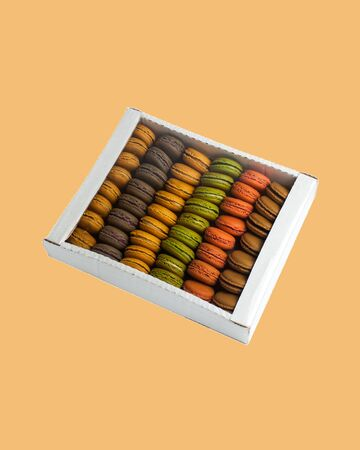 multi-colored pasta macaroons in a cardboard box on a colored background
