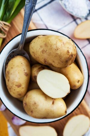 raw potatoes in an enameled bowl with a spoon on a yellow background with a kitchen towel Stock fotó