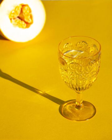 elegant yellow glass with drinking water, wine, tonic, champagne with a hard light on a yellow background with melon Stock Photo