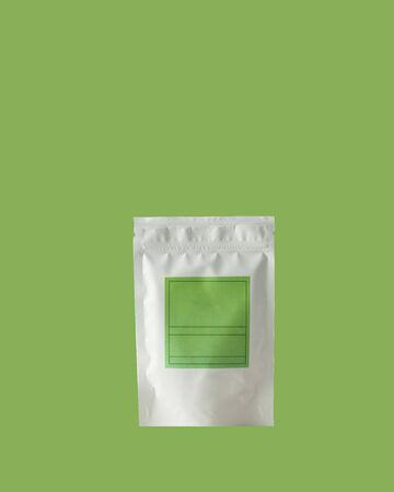 Aluminum bag for tea, coffee, condiments and other bulk substances with green label for signature on green background close-up. Tea bag isolated on green background.