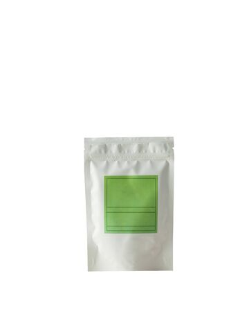 Aluminum bag for tea, coffee, condiments and other bulk substances with green label for signature on white background close-up. Tea bag isolated on white background.