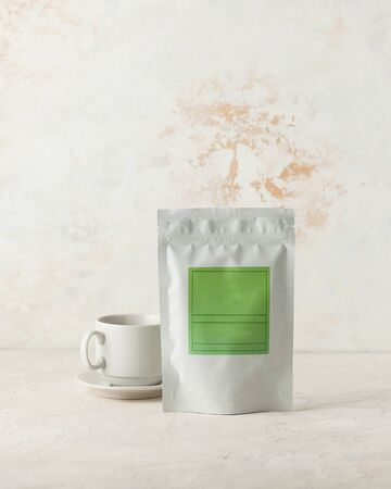 Aluminum bag for tea, coffee, seasonings and other bulk substances with green label for signature on a light background close-up. A tea bag and a white mug on a saucer.