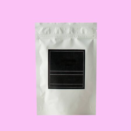 Aluminum bag for tea, coffee, condiments and other bulk substances with black label for signature on pink background close-up. Tea bag isolated on pink background. Foto de archivo
