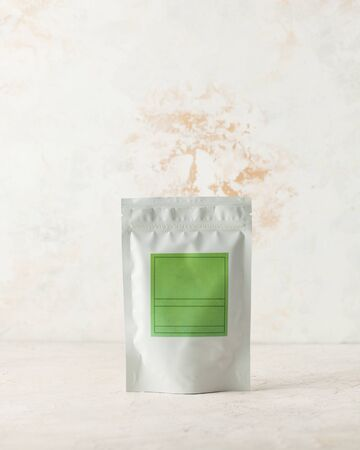 Aluminum bag for tea, coffee, spices and other bulk substances with a green label for signature on a light background.