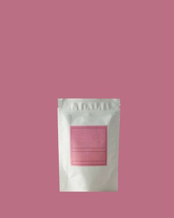 Aluminum bag for tea, coffee, condiments and other bulk substances with pink label for signature on pink background close-up. Tea bag isolated on pink background.