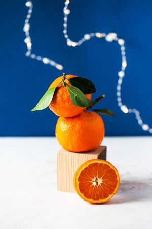 Mandarins close-up on a blue background with space for text. Classic blue color 2020.