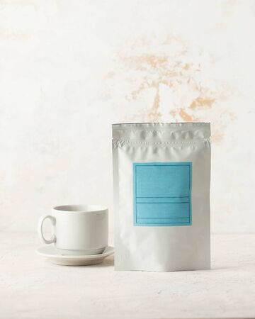 Aluminum bag for tea, coffee, seasonings and other bulk substances with a blue label for signature on a light background close-up. A tea bag and a white mug on a saucer.