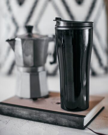 Black thermocup in close-up, with a geyser coffee machine in the background. Vertical photo, the concept of minimalism.
