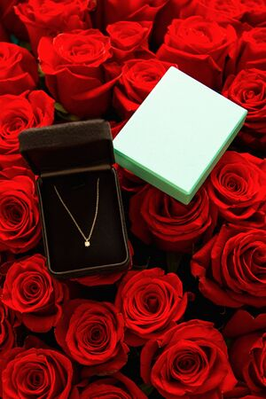 Turquoise gift wrap with a diamond on a chain on a large bouquet of red roses.
