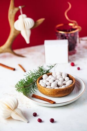 Cranberries in powdered sugar on the Christmas table with Christmas toys, branches of a green Christmas tree on a wooden plate with a bright festive background.