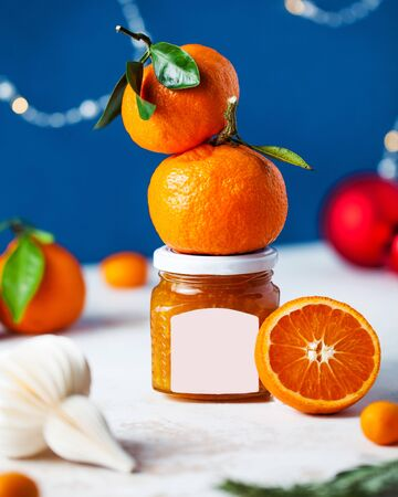 Citrus tangerine jam in a glass jar with a label for typing close-up on a festive Christmas background with Christmas tree toys. Theres fresh citrus on the jar.