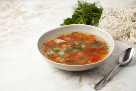 Hot fish soup with potatoes, red bell peppers, carrots and greens in a light plate on a light background. A silver spoon and a bunch of fresh dill. space for text