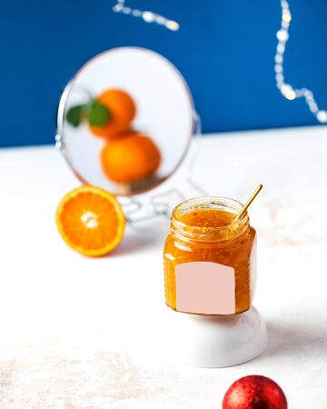 Tangerine jam in a glass jar with a gold spoon. Tangerines are reflected in a round mirror.