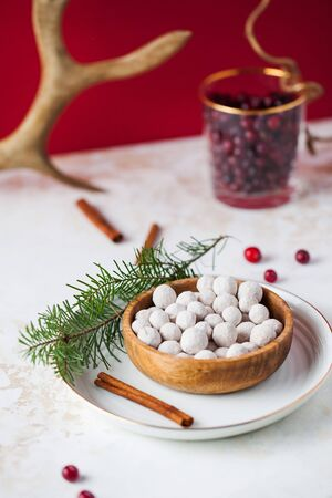 Cranberries in powdered sugar in a wooden plate with a tube of cinnamon and a fir branch. In the background, fresh cranberries and deer horn.
