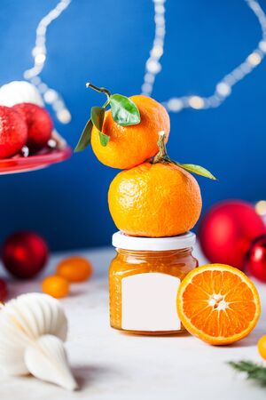 Citrus tangerine jam in a glass jar with a label for typing close-up on a festive Christmas background with Christmas tree toys. There's fresh citrus on the jar.