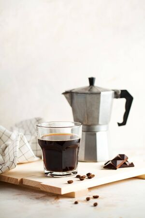 Black coffee, Moka for making espresso, geyser coffee machine on a wooden tray with coffee beans and chocolate, space for text. Photo for a coffee shop on a light background in a minimalist style.