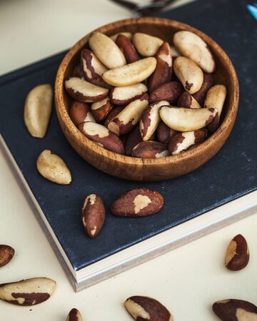 A handful of Brazil nuts in a wooden plate on a light background. Food photo of a healthy snack, dessert for vegetarians.