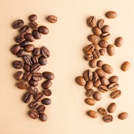 Coffee beans of different varieties close-up on a light brown background. For screensavers, roasters, coffee sellers. Banco de Imagens