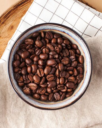 Arabica coffee beans in a ceramic bowl on a wooden tray on a brown background for coffee houses and coffee shops.